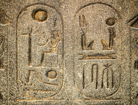 enclosing: Ancient egyptian hieroglyph carved in stone  with cartouches enclosing royal names