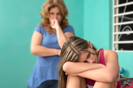 beautiful angry: Sad teenage girl sitting on her bed with her worried mother on the background