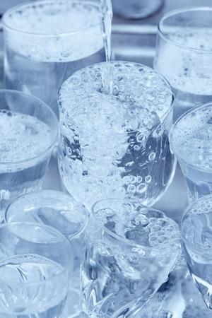 lavar platos: Lavar platos - Material de vidrio bajo un chorro de agua en el fregadero de la cocina