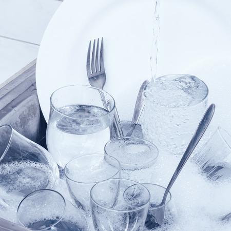 lavar platos: Lavar platos - cristaler�a, cubiertos y platos en el fregadero de la cocina
