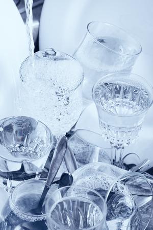 lavar platos: Lavar platos - cristaler�a, cuberter�a y vajilla bajo un chorro de agua en el fregadero de la cocina Foto de archivo