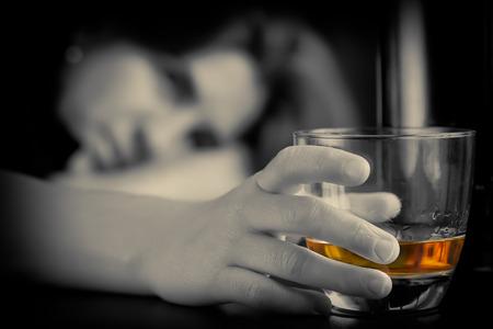 drogadiccion: Borracha y deprimida solitaria mujer con un vaso de whisky con una expresi�n triste