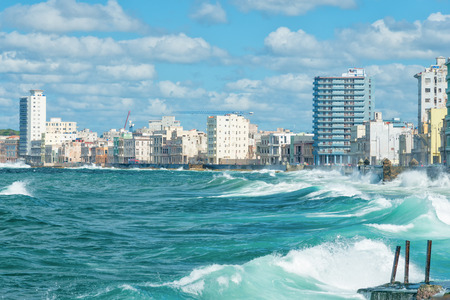 seawall: The Havana skyline with big sea waves crashing on the Malecon seawall