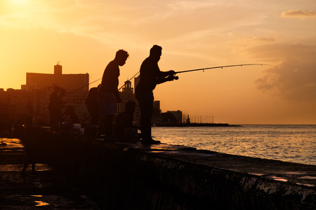 seawall: Beautiful sunset in Havana with the silhouette of group of fishermen on the Malecon seawall Stock Photo