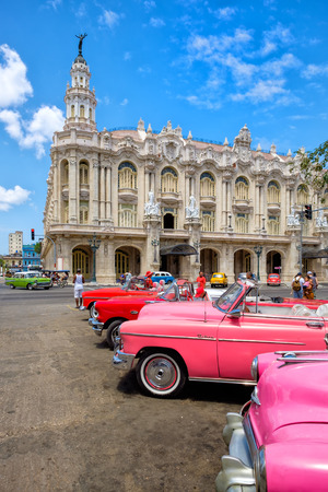 urban art: Classic vintage cars next to the beautiful Great Theater of Havana on a clear sunny day