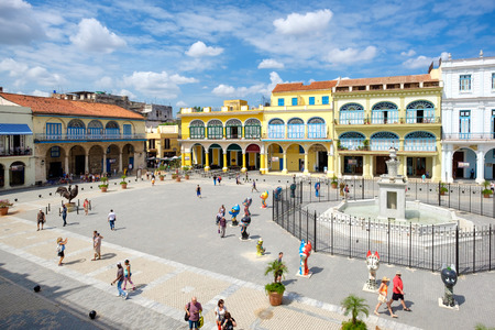 Tourists and cubans at colorful colonial Old Square in the heart of Old Havana Redakční