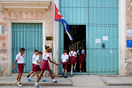 latin child: A group of uniformed cuban children entering a primary school in Old Havana Editorial