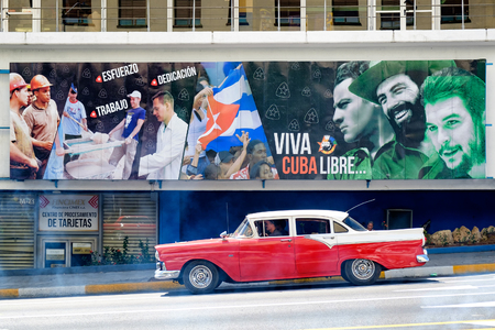 che guevara: Old classic car crosses in front of a billboard with revolutionary slogans in Havana Stock Photo
