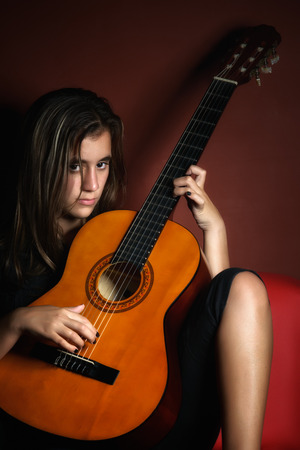 disobedient child: Rebellious teenage girl holding an acoustic guitar photographed in a low key style Stock Photo