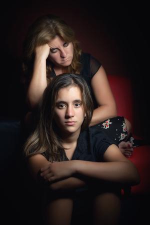 problemas familiares: Adolescente serio con su madre triste y preocupante en el fondo Foto de archivo