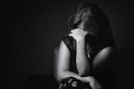 Black and white portrait of a crying sad and depressed woman with a dark background