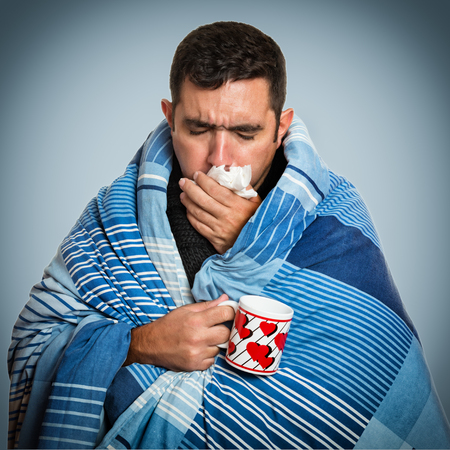 blanket: Portrait of a sick man with the flu, allergy, germs,cold coughing Stock Photo