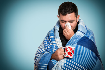 Portrait of a sick man with the flu, allergy, germs,cold, blowing his nose with tissue and holding a warm tea cup 免版税图像