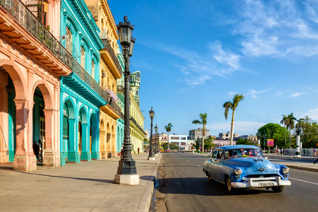habana: Street scene with colorful buildings and old american car in downtown Havana