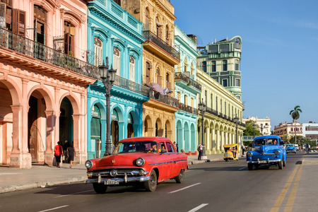 Street scene with colorful buildings and old american car in downtown Havana