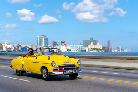 Old convertible car on the Havana malecon avenue with a view of the sea and the city skyline