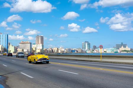 Straatbeeld met oude convertibele auto op de Havana Malecon laan met uitzicht op de zee en de skyline van de stad Stockfoto - 59428510