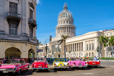 Groep kleurrijke oude klassieke auto's in de buurt van het Capitool in Oud Havana