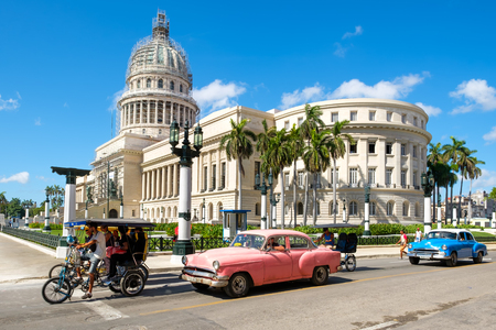 Street scene with classic cars near the Capitol in downtown Havana Foto de archivo