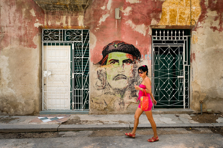 che guevara: Young woman walks in front of a Che Guevara portrait painted on a shabby building in Old Havana