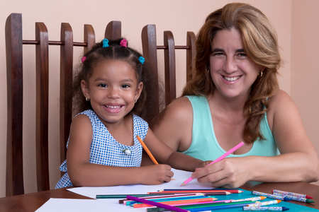 color pencils: Cute multiracial small girl and her mother drawing with color pencils and smiling
