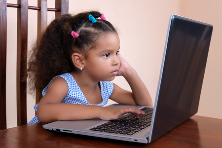 use computer: Cute multiracial small girl using a laptop computer at home