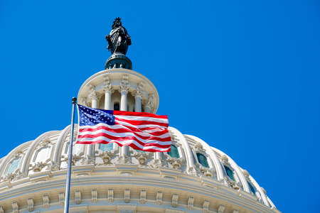 The United States flag waving in front of the Capitol in Washington D.C.