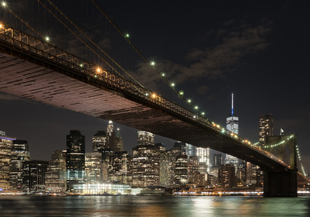 The downtown Mahnattan skyline and the Brooklyn Bridge illuminated at night