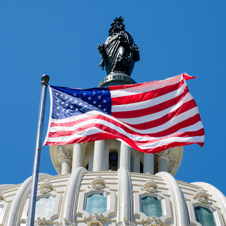 The US National Flag waves in fron of the Capitol building dome featuring the Statue of Freedom in Washington D.C.