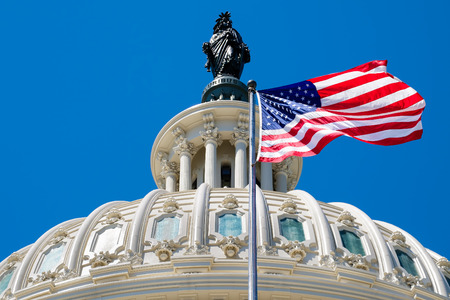 The United States flag waving in front of the Capitol dome in Washington D.C. Stock Photo