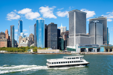 The downtown Manhattan skyline with a boat and a view of the Staten Island Ferry terminal