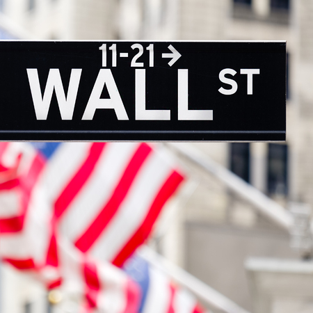 nasdaq: Wall street sign in New York City with out of focus buildings and american flags on the background