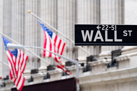 Wall street sign with the New York Stock Exchange and american flags on the background