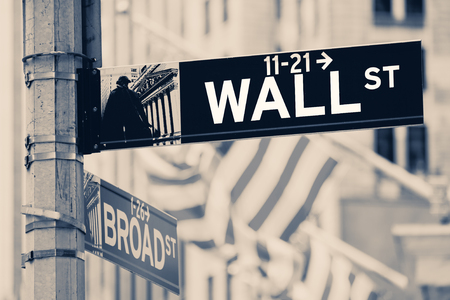 Vintage looking Wall street sign  in New York City with out of focus buildings and american flags on the background Éditoriale