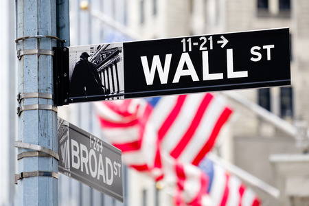 nyse: Wall street sign in New York City with out of focus buildings and american flags on the background