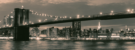 Vintage image of the Brooklyn Bridge illuminated at night with reflections on the East River
