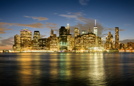 The Lower Manhattan skyline at sunset with reflections on the East River Stock Photo
