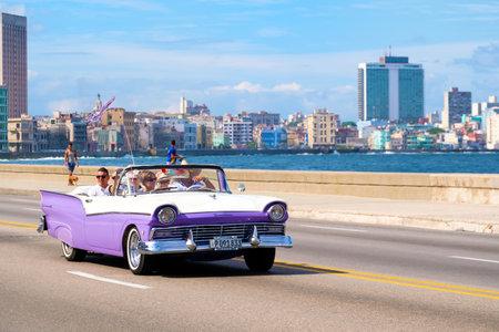 하바나에서 유명한 해변 Malecon 애비뉴에서 클래식 미국 컨버터블 자동차에 타고를 즐기는 관광객 에디토리얼