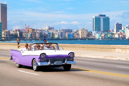 Tourists enjoying a ride on a classic american convertible car  at the famous seaside Malecon avenue in Havana