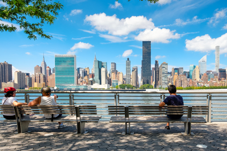 queens: NewYorkers relaxing at a park in Queens with a view of the midtown Manhattan skyline