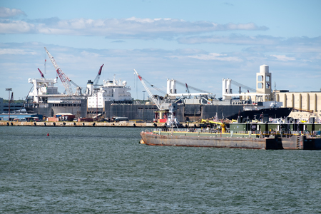 unloading: Pontoons, tugboats and cranes unloading a cargo ship at the New York Harbor Stock Photo
