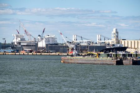 ny: Pontoons, tugboats and cranes unloading a cargo ship at the New York Harbor Stock Photo