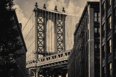old city: Vintage toned famous view of the Manhattan Bridge and a Brooklyn street sidelined by old brick buildings in New York City Stock Photo