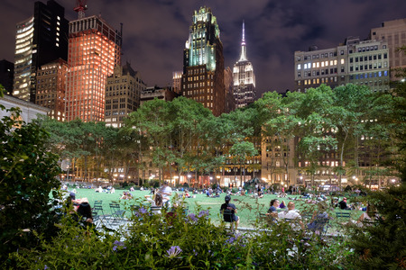 bryant park: Bryant Park in New York City illuminated at night and surrounded by skyscrapers