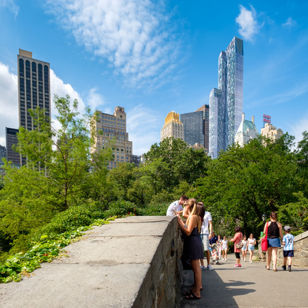 People at a stone bridge in Central Park with the midtown New York skyscrapers on the background Editorial