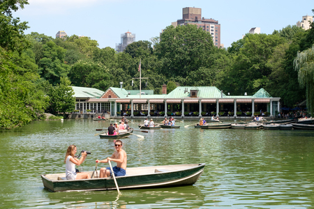 city park boat house: Rowboats at The Lake with a restaurant on the background at Central Park in New York City Editorial