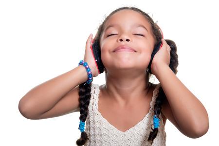 negras africanas: africano americano pequeña niña linda que escucha la música en los auriculares inalámbricos aislados en blanco Foto de archivo