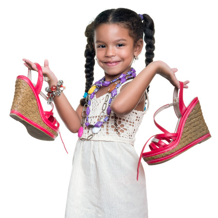 Cute african american small girl dressed up as an adult woman with coloful necklaces carrying a pair of red shoes - isolated on white Imagens