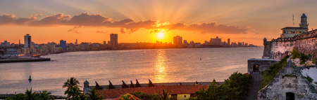 Beautiful sunset in Havana with a view of the city skyline , the El Morro lighthouse and the sun setting over the buildings - Seen from across the bay