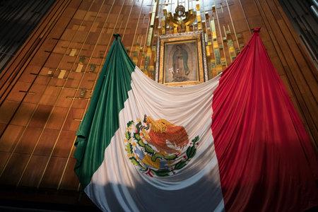 bandera de mexico: Imagen de la Virgen de Guadalupe y una bandera mexicana en la Basílica de Nuestra Señora de Guadalupe en Ciudad de México